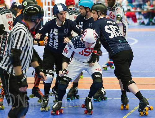 15 MAR 2014 - BIRMINGHAM, GBR - Team USA jammer Jonathan R (in white, blue and red) forces his way past Power or Scotland blockers during the bout between the two countries at the inaugural Men's Roller Derby World Cup in the Futsal Arena in Birmingham, West Midlands, Great Britain (PHOTO COPYRIGHT © 2014 NIGEL FARROW, ALL RIGHTS RESERVED)