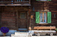 Typical Swiss wooden chalet style house with straw brush in Serneus near Klosters in Graubunden region, Switzerland