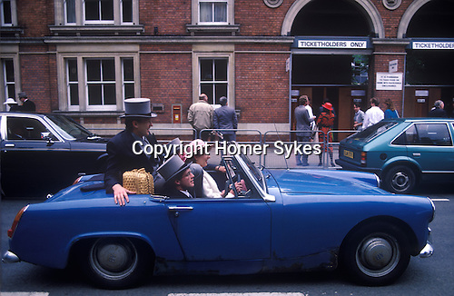 Royal Ascot. Racegoers leave after a day at the races squashed into an old Ausin Healey car. 1980s. Ascot Berkshire UK.