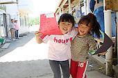 May 18, 2011; Minamisanriku, Miyagi Pref., Japan - Ruka Sato (L), 5 and Sena Sato, 4, hold up cards sent from a school in Los Angeles at the Shizukawa High School Evacuation Center in Minamisanriku after the magnitude 9.0 Great East Japan Earthquake and Tsunami that devastated the Tohoku region of Japan on March 11, 2011.