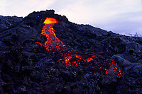 Large tube breakout sends stream of lava into the early morning light, Hawaii Volcanoes National Park, Big Island, Hawaii, USA