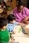 Education preschool 3-4 year olds female teacher helps boy assemble puzzle another boy looking on and learning through observation vertical