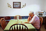 Mary Deaton rests her hand on her face early Friday morning in the reception room of the Deaton Funeral Home in Jackson, Ky, Oct. 14, 2011. Deaton woke up around 1:30 a.m. to help service a new body. She would not be able rest again until after a funeral later that morning. Photo by Brandon Goodwin