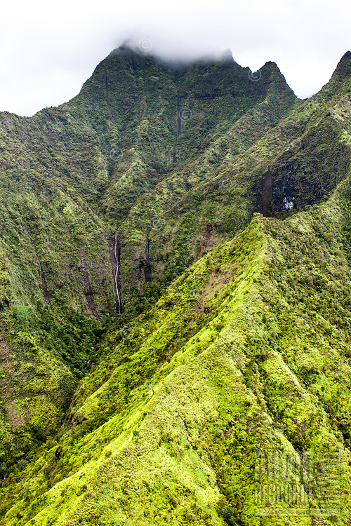 A waterfall inside a valley of a green mountain range on Kaua'i