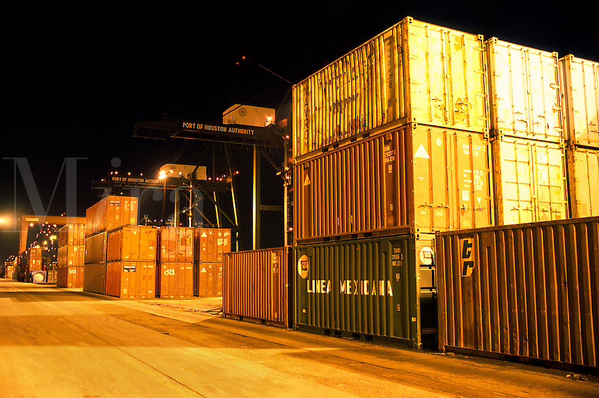 Cargo containers stacked at a shipping terminal light up at night.