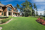a large, lodge like estate sized home sits under a summer blue sky with a lawn of perfectly manicured green grass fronted by a curved border of mixed annuals, perennials and shrubs, and mature evergreen trees behind