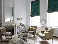 A pair of Marquise-style armchairs make a statement amidst the eclectic furnishings of the living room