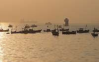 Fishing boats lie at anchor around Dolphin Rock Lighhouse in Mumbai, India