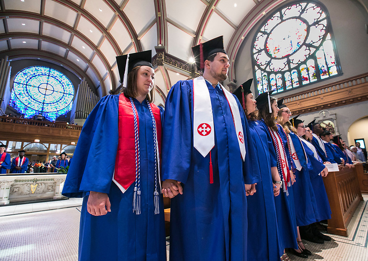 English major Jordan Battaglia, left, and Ben Gartland, a College of Communication graduate, stand with their fellow students in the glow of the stained glass of the Saint Vincent de Paul Parish Church on DePaul University's Lincoln Park Campus Friday, June 9, 2017, during the Baccalaureate Mass. The event was part of the 119th commencement ceremonies for the Chicago university. (DePaul University/Jamie Moncrief)