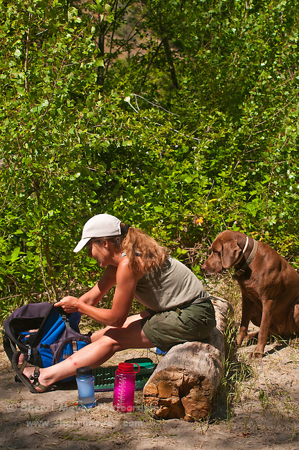 Woman unpacking her picnic lunch from her daypack, while her dog watches, North Fork of the American River, Weimar, California.