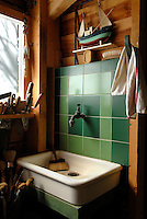 The wall behind the antique ceramic sink in this corner of the atelier has been covered with practical green tiles