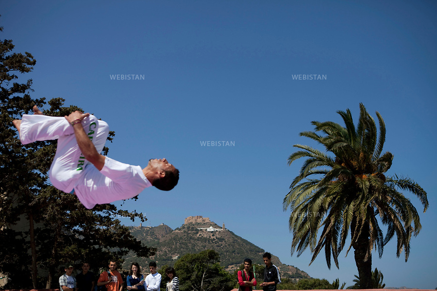 Algerie. Oran. 16  Avril 2011.Saut acrobatique d'un danseur de capoeira admire par les spectateurs. Au second plan, une vue sur la colline Aidour.<br /> <br /> <br /> Algeria, Oran. April 16th 2011<br /> A capoeira acrobat jumps in the air while being admired by spectators. In the background is a view of the Aidour hills.