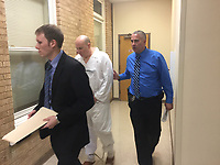 Northwest Arkansas Democrat-Gazette/TRACY M. NEAL Kevin Lammers, a Benton County deputy public defender, walks in front of Grant Hardin who is being escorted into court by Larry Taylor, a Rogers police detective. Hardin was arrested Monday in connection with the 1997 rape of a Rogers school teacher.