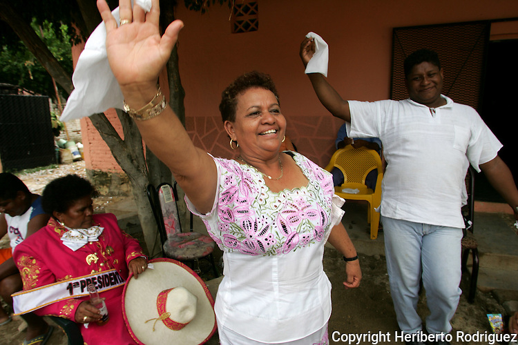 Mrs. Sara Camero dances with a neighbor as she celebrates as the newly President of the Mayordomia of Santiago Apostol after Mrs Marcelina Salinas (sitting in background) delivered her mandate in Cuajinicuilapa town, in Costa Chica in southern state of Guerrero. Mrs. Salinas delivered her mandate to the new President Sara Camero during the festivities to pay honor to Santiago Apostol, one of the patron saints of this AfroMexican town. Photo by Heriberto Rodriguez ..