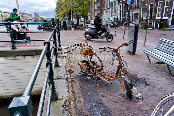 burned out and totally destroyed scooter, Amsterdam near the Magere Brug