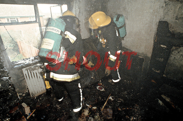 Firefighters wearing BA having extinguished the severe fire are searching through a burning house for possible occupants. This image may only be used to portray the subject in a positive manner..©shoutpictures.com..john@shoutpictures.com