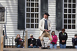 A period actor in Colonial Williamsburg, Virginia shows female visitors how to curtsey.
