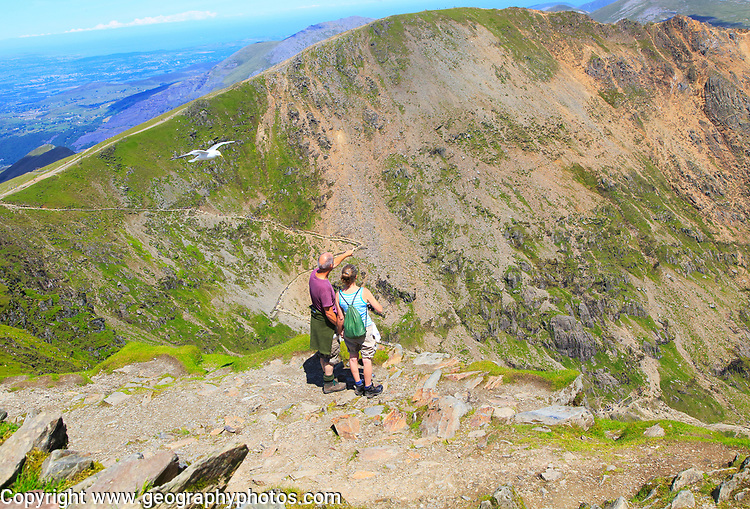 Man and woman enjoying view from summit of Mount Snowdon, Gwynedd, Snowdonia, north Wales, UK