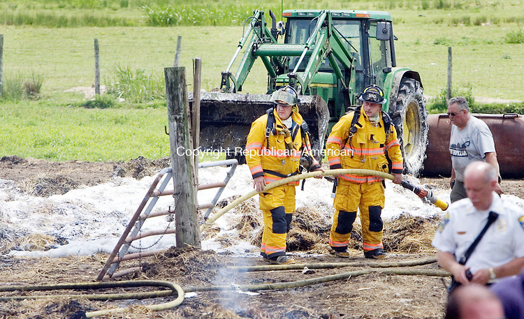 WATERTOWN CT. 21 June 2013-062113SV03-Firefighters extinguish the remains of a hay wagon that caught fire at 360 Sandbank Road in Watertown Friday. The wagon was in a barn but was pulled out before the barn could catch fire. <br /> Steven Valenti Republican-American