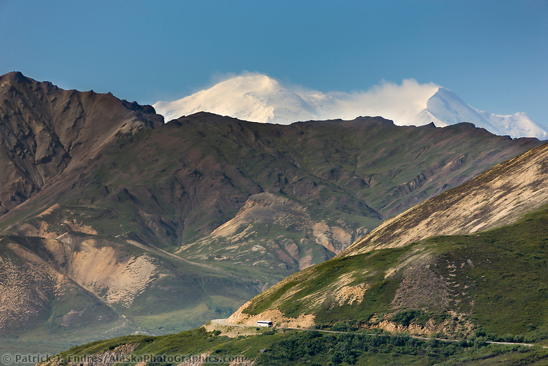 North And South Summits Of Mt. Denali Loom Over The Hills Near Polychrome Pass. Tour Bus Travels Along The Park Road, Denali National Park, Interior, Alaska.