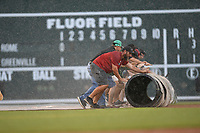Greg Burgess, foreground, head of operations and grounds at the Greenville Drive, pulls the tarp with other staffers during a sudden downpour at a game on Friday, August 3, 2018, at Fluor Field at the West End in Greenville, South Carolina. (Tom Priddy/Four Seam Images)