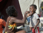 A survivor of the January 12 earthquake brushes her daughter's teeth amidst the rubble in the Port-au-Prince neighborhood of Belair.