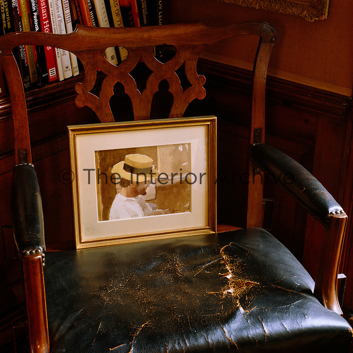 A framed watercolour of a man has been placed on a worn leather armchair in a corner of the library