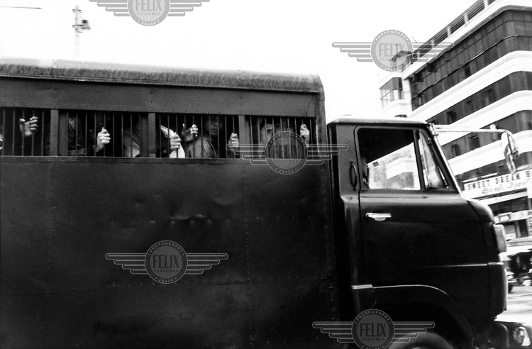 Prisoners are carted away in a police van in Taungyi.