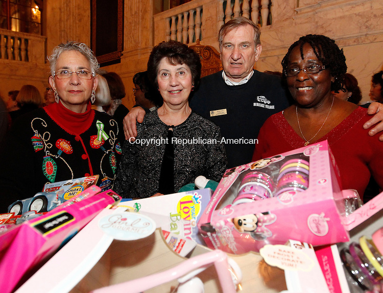 Waterbury, CT-19 December 2012-121912CM02-  Left to right, Terry Longo, of Waterbury, Jo Ann Sullivan of Watertown, Ron Conti of Southbury and Margaret Holmes of Oakville and volunteers at the Palace Theater of Waterbury pose for a photo behind a bin of donated toys Wednesday night at the Palace Theater in Waterbury.  The Palace Theater hosted it's annual holiday gathering for its volunteers and staff members who donated toys which will be given to New Opportunities of Waterbury.  The toys will then be distributed to children in need. Christopher Massa Republican-American