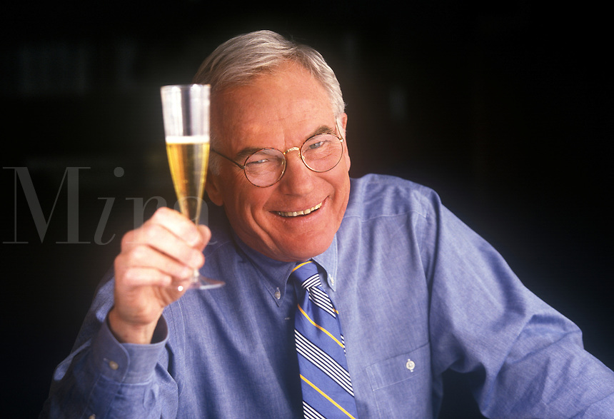 Satisfied businessman toasts with a glass of champagne.
