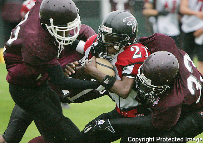 Manatee Mustangs Jonathan Brooks (22) and Waymon Bowden (33) drag West Valley Falcon Myles Johansen (21) to a stop during the Pop Warner Super Bowl at Disney's Wide World of Sports complex in Orlando, FL, Friday, Dec. 9, 2005.(AP Photo/Brian Myrick)