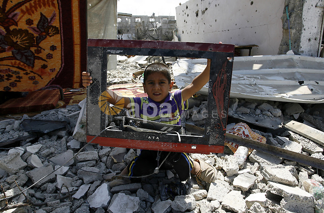 """A Palestinian boy holds a damaged television on the rubble of a destroyed house in Khan Yunis in the southern Gaza Strip on September 11, 2014. Israel's deputy foreign minister,Tzahi Hanegbi , warned that Hamas was likely to resume """"violence"""" if it feels it has made no political gains from upcoming talks in Cairo. Photo by Abed Rahim Khatib"""