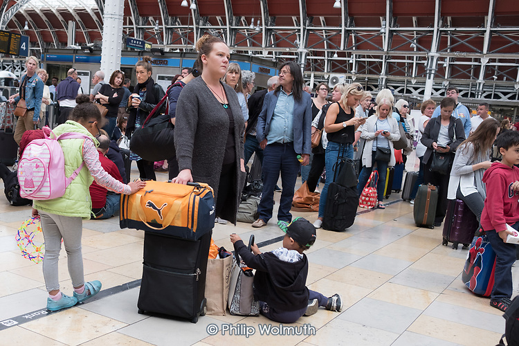 Passengers wait for a delayed GWR train at Paddington Station, London.