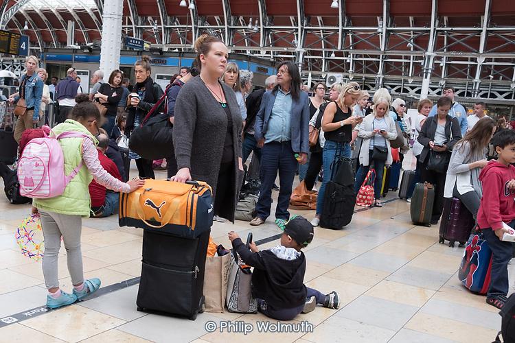 Passengers wait for a delayed GWR train at Paddington Station, London.