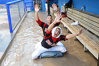 Batavia Muckdogs outfielder Austin Dean (3) and pitcher Trevor Williams (46) use the garbage can as a floatation device when the dugout flooded during a brief but heavy rain storm during a game against the Hudson Valley Renegades on August 8, 2013 at Dwyer Stadium in Batavia, New York.   The game was called due to unplayable field conditions.  (Mike Janes/Four Seam Images)