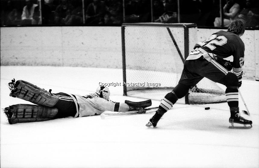 St.Louis Blues #22 Danny O'Shea tries to score on Seals goalie Gilles Meloche. (1972 photo/by Ron Riesterer)