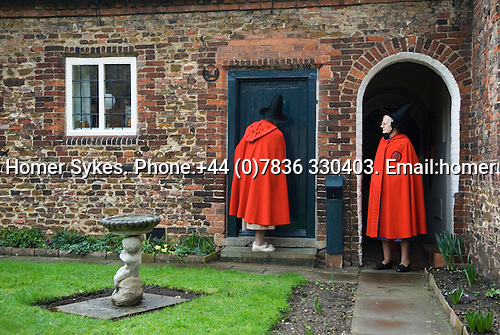 Old Ladies of Castle Rising. The Hospital of the Holy and Undivided Trinity Almshouses, Castle Rising, Norfolk, England 2007. Founders Day. The ladies wear tradiotional red cloaks and pointed black hats.