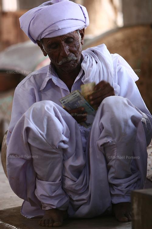 03.10.2008 Dwarka(Gujarat)<br /> <br /> Man counting his money in the market.<br /> <br /> Homme en train de compter son argent au march&eacute;.