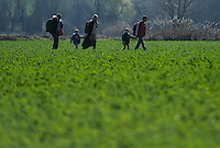Pictured: Migrants of all ages, carrying their belongings, make their way through fields to Idomeni, Greece Wednesday 02 March 2016<br /> Re: More migrants have been arriving at the Greek FYRO Macedonian border of Idomeni, Greece.