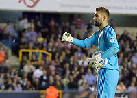 Goalkeeper Bartosz Bialkowski of Ipswich Town throws a lighter off the pitch that is thrown at him during the Sky Bet Championship match between Millwall and Ipswich Town at The Den, London, England on 15 August 2017. Photo by Alan  Stanford / PRiME Media Images.