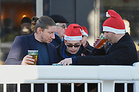 Race goers study the form in festive mood during Horse Racing at Plumpton Racecourse on 2nd December 2019