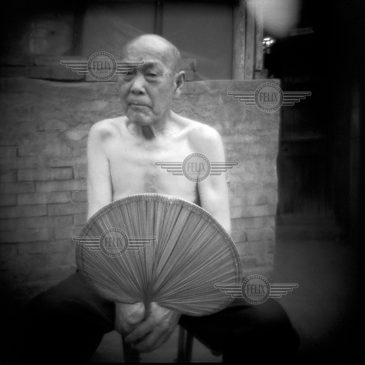 An elderly man with a fan is pictured outside his home in a hutong neighbourhood. The traditional hutong housing areas are being systematically demolished to make way for new modern developments in the city.