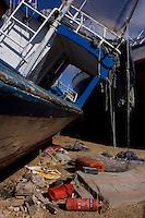 Cimitero delle barche...I barconi che trasportano i profughi vengono depositati in tre punti dell isola in attesa di essere smaltiti. ..Indumenti e oggetti vari sparsi vicino alle barche depositate nei pressi del porto...Lampedusa 05 Marzo 2011...Photo Serena Cremaschi Insidefoto..........