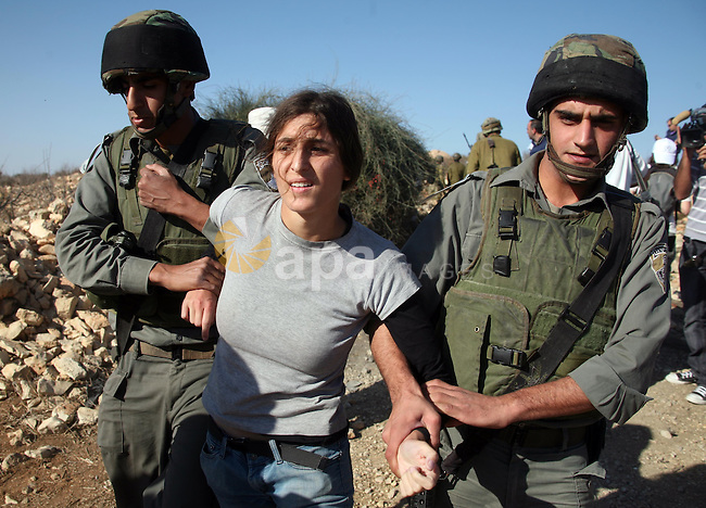 Israeli soldiers disperse foreign activists during a demonstration by Palestinian, Israeli and foreign activists against the demolishing of farm land to be used in the construction of Jewish settlements near the existing Israeli settlement of Karmi Tsur near the Palestinian village of Beit Omar, just north of the West Bank town of Hebron on November 20, 2010. Photo by Najeh Hashlamoun