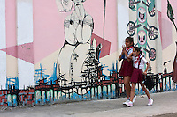 Cuba, Cienfuegos.  School Girls Walking Past Mural Art.  The girls' red skirts identify them as primary school students.