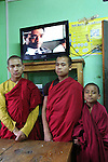 Buddhist monks watching television after dinner at Nalanda Buddhist Monastery, Punakha, Bhutan..Bhutan the country that prides itself on the development of 'Gross National Happiness' rather than GNP. This attitude pervades education, government, proclamations by royalty and politicians alike, and in the daily life of Bhutanese people. Strong adherence and respect for a royal family and Buddhism, mean the people generally follow what they are told and taught. There are of course contradictions between the modern and tradional world more often seen in urban rather than rural contexts. Phallic images of huge penises adorn the traditional homes, surrounded by animal spirits; Gross National Penis. Slow development, and fending off the modern world, television only introduced ten years ago, the lack of intrusive tourism, as tourists need to pay a daily minimum entry of $250, ecotourism for the rich, leaves a relatively unworldly populace, but with very high literacy, good health service and payments to peasants to not kill wild animals, or misuse forest, enables sustainable development and protects the country's natural heritage. Whilst various hydro-electric schemes, cash crops including apples, pull in import revenue, and Bhutan is helped with aid from the international community. Its population is only a meagre 700,000. Indian and Nepalese workers carry out the menial road and construction work.