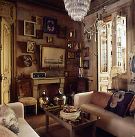 A traditional sitting room with two modern sofas in neutral upholstery are set either side of a coffee table with a mirror top. A collection of various artworks are displayed on one wall above a table. A pair of French doors leads to another room.