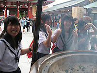 """School Girls"".  School girls fan smoke from a huge incense pot for good health at Sensoji (Asakusa Kannon Temple),  Tokyo"