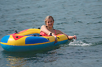Aberystwyth Wales UK, Thursday 12 May 2016<br /> UK Weather: A young woman in an inflatable dinghy in the sea at the seaside in  Aberystwyth, on the Cardigan Bay coast of west Wales, enjoying a last day of warm weather in the current mini-heatwave. <br /> The temperatures are set to fall over the coming days, with bright but colder conditions prevailing over the country