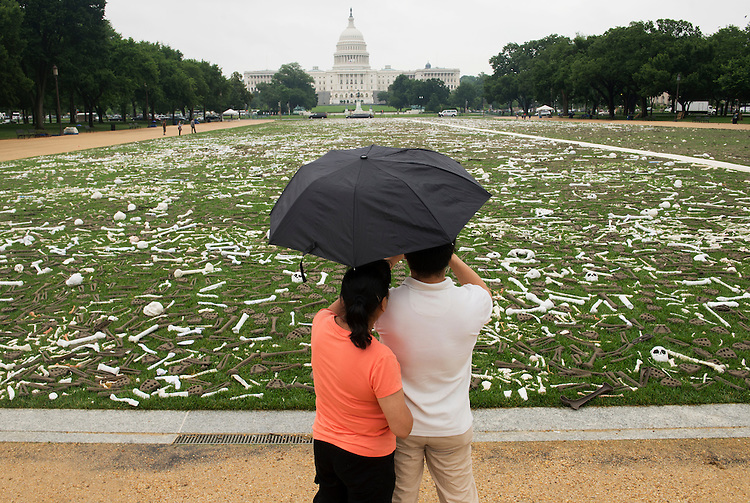 UNITED STATES - JUNE 10: Visitors take pictures at the One Million Bones installation on the National Mall. The three-day exhibit is meant to raise awareness of genocide and violence that occurs around the world in countries like Sudan, Somalia, and Burma. (Photo By Tom Williams/CQ Roll Call)